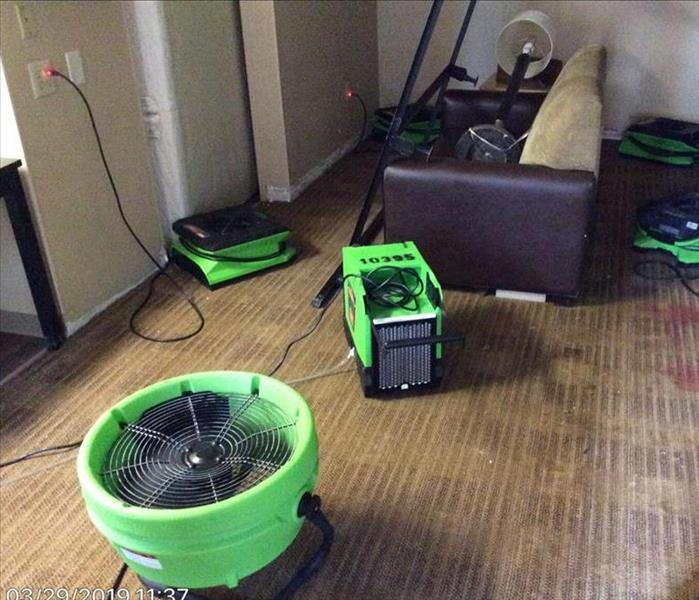 hotel room with wet carpet and green drying equipment scattered through out the room