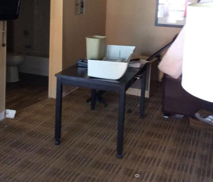 hotel room with all furniture moved into center of room with dry carpet and no drying equipment